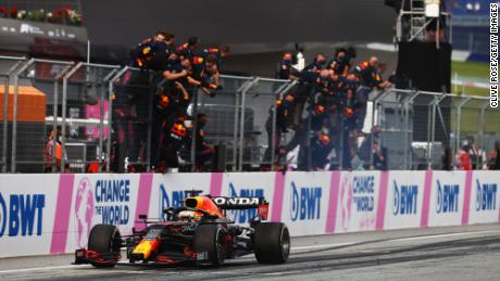 Verstappen takes the chequered flag as his team celebrate on the pitwall at the Styrian Grand Prix.