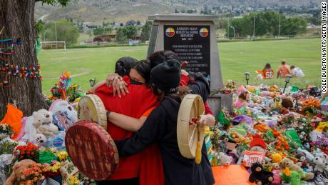 People from Mosakahiken Cree Nation hug in front of a makeshift memorial at the former Kamloops Indian Residential School, where the remains of 215 indigenous children were discovered in May.