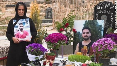 Navid's mother (left) stands by Navid's grave in March 2021 in Shiraz, Iran.