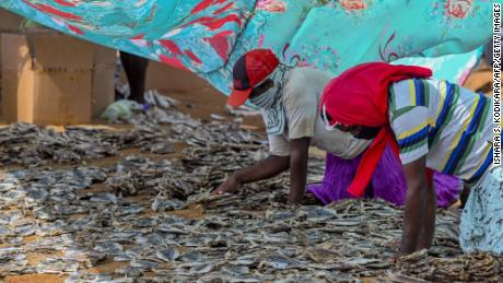 Workers process salted fish in Negombo, where plastic raw materials and other debris washed ashore.