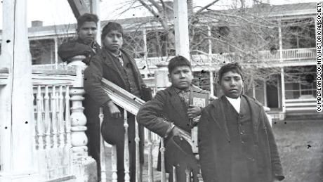 Four male students pose on the grounds of the Carlisle Indian Industrial School in 1879.  The remains of Dennis Strikes First (Blue Tomahawk), second from left, will be repatriated to the Rosebud Sioux Reservation next week.