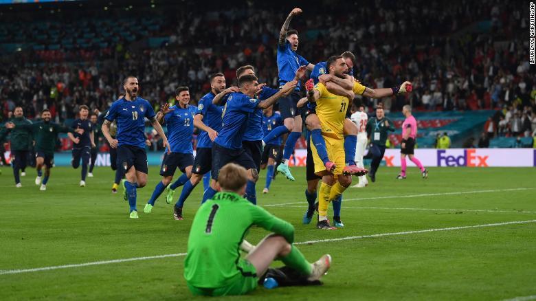 Italian players celebrate after Bukayo Saka's penalty is saved.