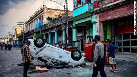 A police car is overturned during a demonstration against Cuban President Miguel Diaz-Canel in Havana on July 11.