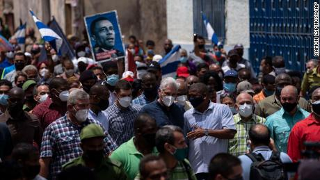 President Miguel Diaz-Canel (in dark blue shirt, wearing a mask) walks with supporters Sunday after an anti-government protest in San Antonio de los Banos, Cuba.