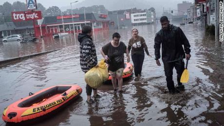 Residents use rubber rafts to evacuate after the Meuse River broke its banks during heavy flooding in Liège, Belgium, on Thursday.