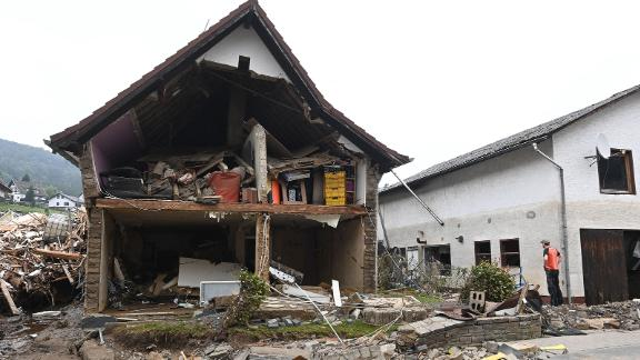 A man stands in front of a destroyed house in Schuld, Germany.