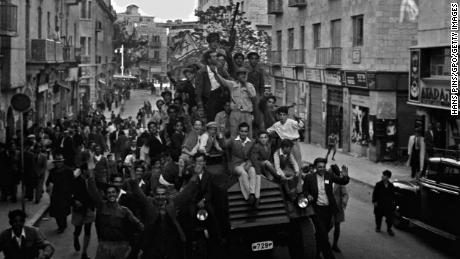 Jubilant residents in the Jewish part of Jerusalem ride a police car and wave what would become the Israeli flag as they celebrate the UN's 1947 decision to approve the partition of Palestine in the British Mandate for Palestine. (Photo by Hans Pins/GPO via Getty Images)