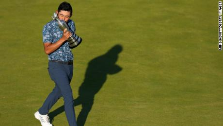 Morikawa celebrates with the Claret Jug on the 18th green after winning the Open.