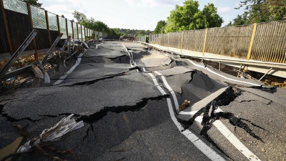 A damaged road buckles after flooding in Euskirchen, Germany.