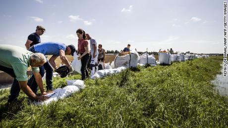 ہالینڈ کے صوبہ لیمبرگ میں شدید بارش اور سیلاب کے بعد لوگ سیلاب کے تھیلے کا استعمال کرتے ہوئے سیلاب سے دفاع کرتے ہیں۔