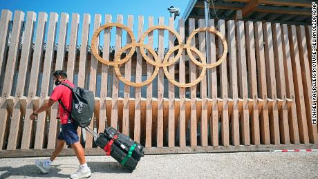 A man walks past Olympic rings at the entrance to Olympic Village.