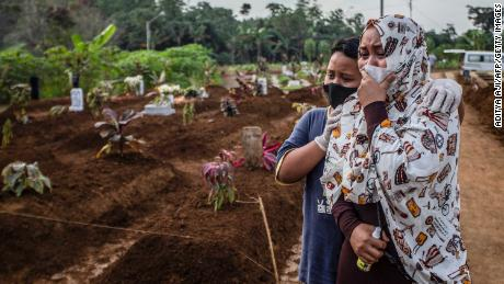 A mother mourns with her son during her mother's funeral at the Mulyaharja cemetery for Covid-19 coronavirus victims, in Bogor, West Java, on July 8, 2021.