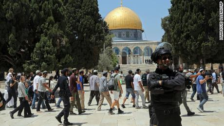 An Israeli police officer stands guard as Jewish men visit the Dome of the Rock on the Temple Mount/Haram al-Sharif compound, during the annual mourning ritual of Tisha B'Av (the ninth of Av) -- a day of fasting and a memorial day, commemorating the destruction of ancient Jerusalem temples, in the Old City of Jerusalem, on Sunday, July 18.