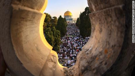 """Palestinian worshipers perform the al-Adha feast prayer at the al-Aqsa Mosque complex in Jerusalem's old city, on the first day of the feast celebrated by Muslims worldwide, on July 20, 2021. The Eid al-Adha, or """"Feast of Sacrifice,"""" marks the end of the annual pilgrimage or Hajj to the Saudi holy city of Mecca and is celebrated in remembrance of Abraham's readiness to sacrifice his son to God."""