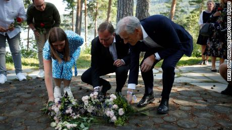 Leader of the youth organization of the Labour Party (AUF) Astrid Hoem, left, Swedish Prime Minister Stefan Löfven, center, and leader of the Norwegian Labor Party Jonas Gahr Store, right, lay flowers at a memorial on Utoya island, on July 21, 2021.