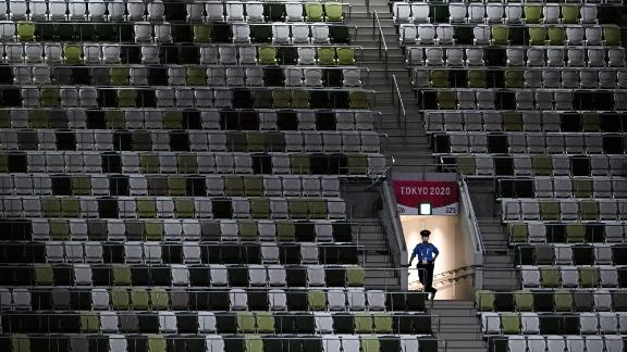 A police officer is seen in the mostly empty stadium on July 23. Organizers said that for the opening ceremony, only 950 VIPs would be present in a stadium that can seat nearly 70,000 people.