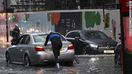 A car is pushed through floodwaters in London's Nine Elms district.