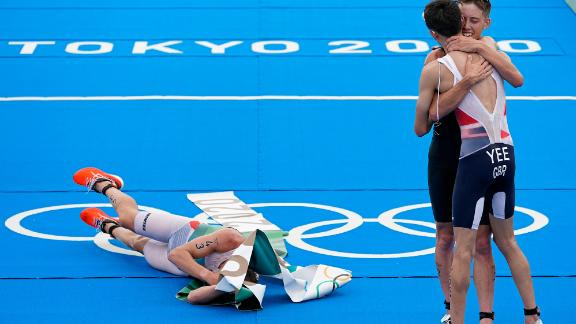 Norway's Kristian Blummenfelt lies on the ground wrapped in finish-line tape after he won the triathlon on July 26. On the right, silver medalist Alex Yee of Great Britain hugs bronze medalist Hayden Wilde of New Zealand.