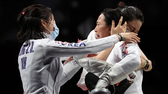 South Korean fencer Kang Young-mi, right, is congratulated by her teammates after they defeated the United States in the epée quarterfinals on July 27.