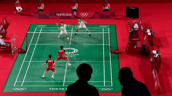 Members of the media are pictured in the foreground as Indonesia's Marcus Fernaldi Gideon, bottom left, and Kevin Sanjaya Sukamuljo play a badminton match against Taiwan's Lee Yang, top left, and Wang Chi-lin on July 27.