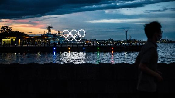 A man in Yokohama, Japan, walks past the Olympic rings lit up at dusk on July 27.