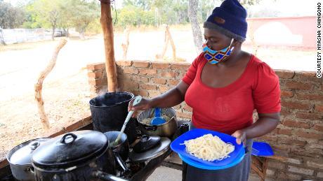 Pauline Chinyandura serves a platter of lunch.
