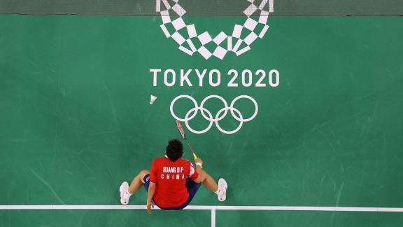 Japanese badminton player Arisa Higashino, top, hits a shot toward China's Huang Dongping in a mixed-doubles semifinal on July 29.