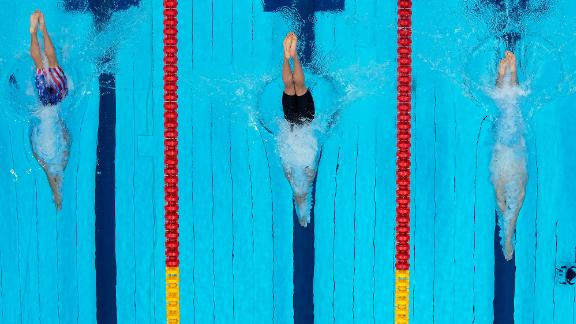 From left, the United States' Bobby Finke, Ukraine's Mykhailo Romanchuk and Germany's Florian Wellbrock dive in the water at the start of the 800-meter freestyle final on July 29. Finke won gold after a late rally.