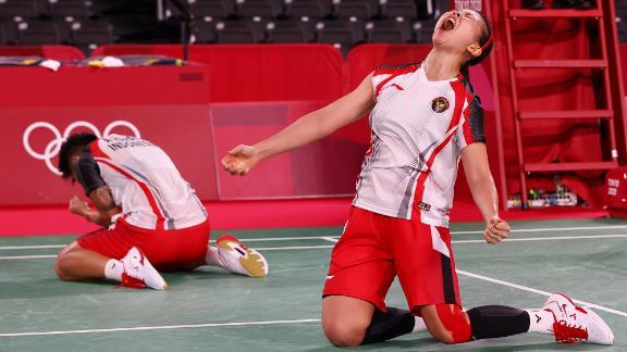 Indonesian badminton players Apriyani Rahayu and Greysia Polii react after winning their quarterfinal match on July 29.