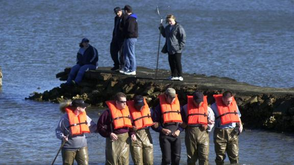 Private detectives comb a portion of Galveston Bay in search of Morris Black's remains in February 2002.