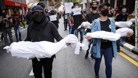 Protesters hold fake corpses during a demonstration near Independence Square in Kuala Lumpur, demanding the resignation of the prime minister over his handling of the coronavirus pandemic.