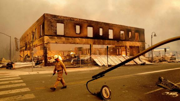 A firefighter passes the Sierra Lodge on Wednesday as the Dixie Fire burns through Greenville.