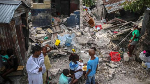 A family eats breakfast in front of homes destroyed by a 7.2 magnitude earthquake in Les Cayes, Haiti, on Sunday, August 15.