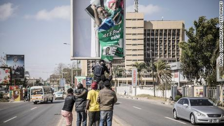 Supporters of Zambian President elect for the opposition party United Party for National Development (UPND) Hakainde Hichilema remove a poster of the former president Edgar Lungu from a pole in Lusaka, on August 16, 2021.