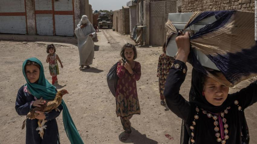 An Afghan woman and her children carry their belongings after fleeing their home in Kandahar on August 4.