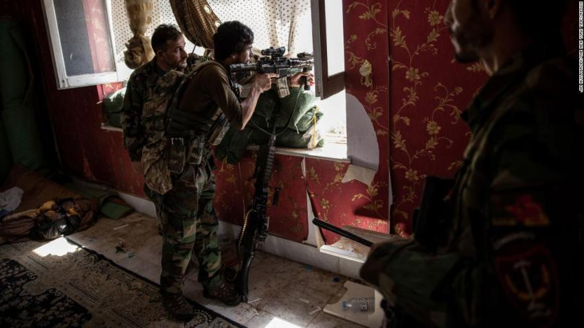 Afghan commandos look out from a window at a home in Kunduz on July 6. The Taliban were moving rapidly to take over districts in northern Afghanistan.