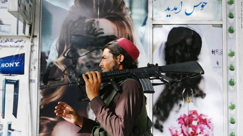 """A Taliban fighter walks past a beauty salon in Kabul where images of women had been defaced by spray paint. As news broke that the Taliban had captured Kabul, some images of uncovered women <a href=""""https://www.cnn.com/2021/08/16/middleeast/kabul-streets-taliban-regime-intl/index.html"""" target=""""_blank"""">were painted over in the Afghan capital.</a> When the Taliban last ruled in Afghanistan, women were barred from public life and only allowed outside when escorted by men and dressed in burqas."""