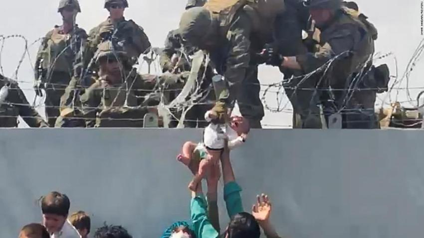 """In this still image taken from <a href=""""https://www.cnn.com/videos/world/2021/08/20/kth-kabul-airport-wall-baby-afghanistan-ac360-vpx.cnn"""" target=""""_blank"""">a video posted to social media,</a> a baby is handed to American troops over the perimeter wall of the airport in Kabul on August 19. Maj. James Stenger, a spokesman for the Marines, <a href=""""https://www.nytimes.com/2021/08/20/world/asia/afghanistan-kabul-baby.html"""" target=""""_blank"""">confirmed to The New York Times</a> that the baby received medical treatment and was reunited with their father at the airport."""