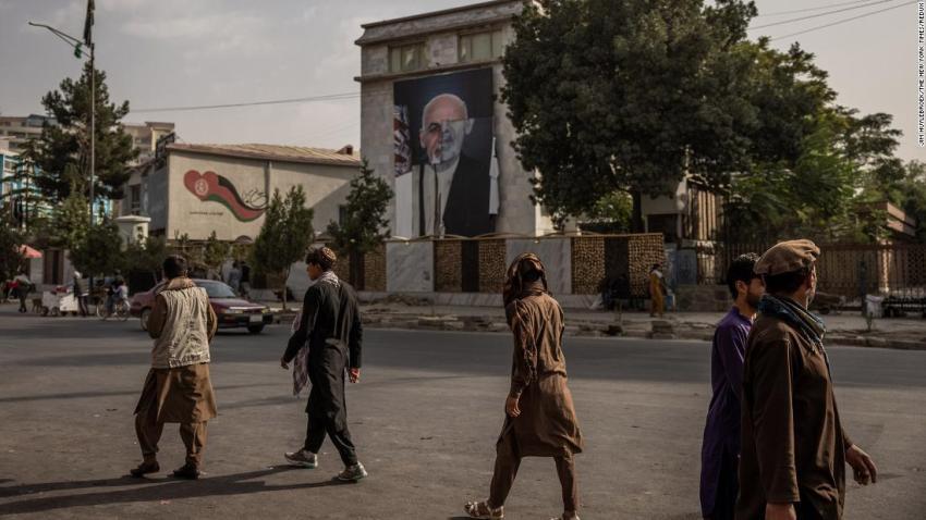 People walk past a half-destroyed poster of former Afghan President Ashraf Ghani in Kabul on August 18.