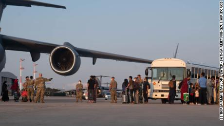 A group of Afghan evacuees depart a C-17 Globemaster III aircraft at Ramstein Air Base, Germany, Aug. 20, 2021.