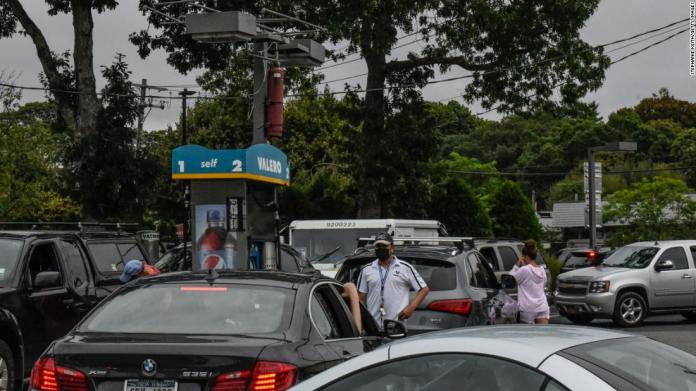 People line up to fuel their cars at a gas station in Westhampton, New York, on August 21.