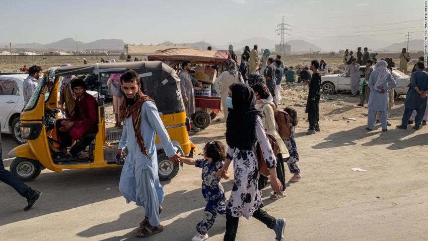 People gather outside the airport in Kabul as a military transport plane takes off on August 21.