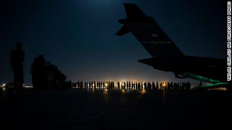 A US Air Force air crew prepares to load evacuees aboard a C-17 Globemaster III transport aircraft at Hamid Karzai International Airport in Kabul on August 21.