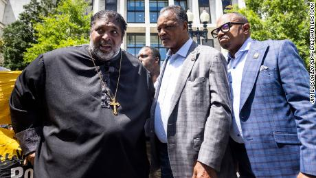 """Political activists Reverend William J. Barber II (L) and Reverend Jesse Jackson (C) speak prior to being detained for obstructing traffic during a """"Moral March on Manchin and McConnell"""" in Washington, DC, on June 23, 2021."""