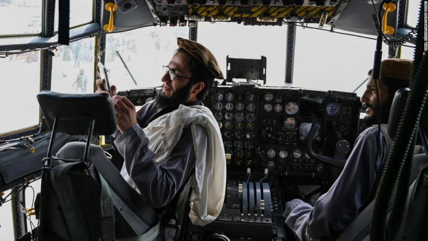 Taliban fighters sit in the cockpit of an Afghan Air Force aircraft that was left behind at the airport in Kabul on August 31.