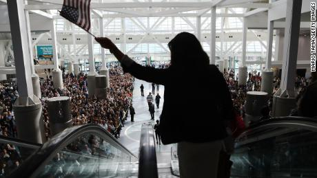 A new US citizen waves an American flag while departing a naturalization ceremony on March 20, 2018, in Los Angeles.