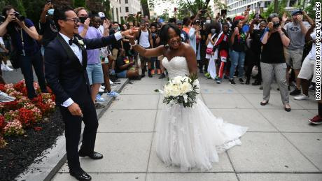 Waizeru Johnson holds her new husband's hand as she passes a group of people celebrating the Juneteenth holiday at Black Lives Matter Plaza in Washington on June 19, 2021.