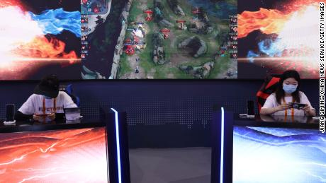 """Visitors playing """"Arena of Valor,"""" a multiplayer online battle arena game, at Tencent's booth during a trade fair in September in Beijing."""