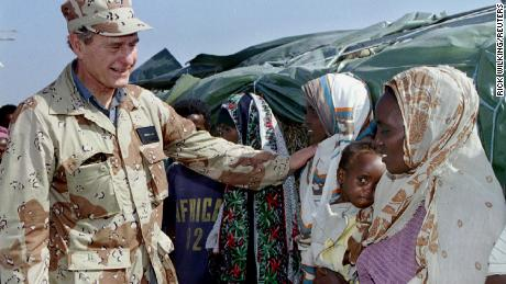 Then US President George H.W. Bush greets Somalian women while visiting US troops in Somalia in January 1993.