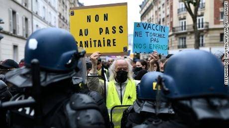 """A protester holds signs reading, """"No to the health pass"""" and """"Vaccine: keep away from our children,"""" at a demonstration in the western Paris suburb of Neuilly-sur-Seine on August 7."""